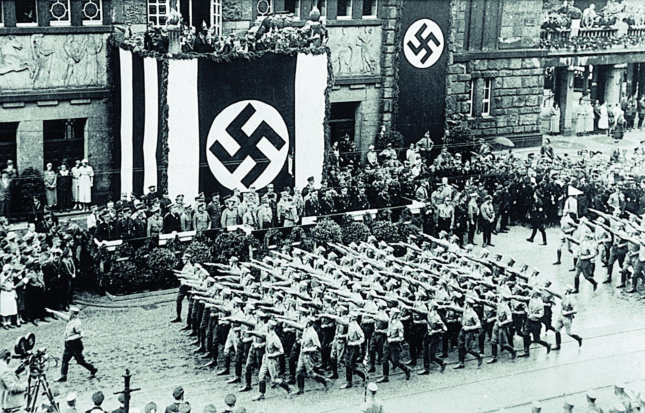 Die SA marschiert in Dortmund vor dem Stadttheater auf, angeführt von SA-Chef Ernst Röhm. Unter dem Hakenkreuz erkennbar: Adolf Hitler.